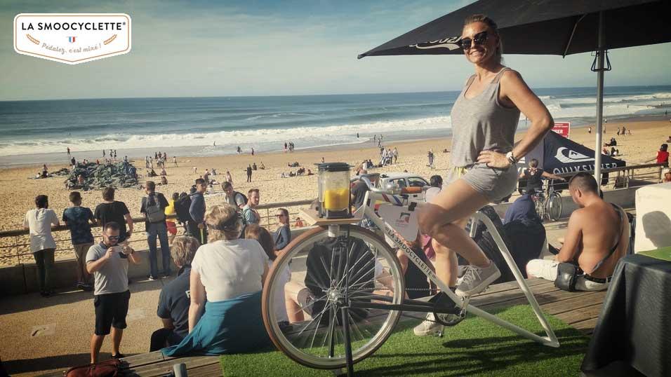 Une jeune femme pose fièrement sur notre Smoocyclette lors du championnat mondial de Surf